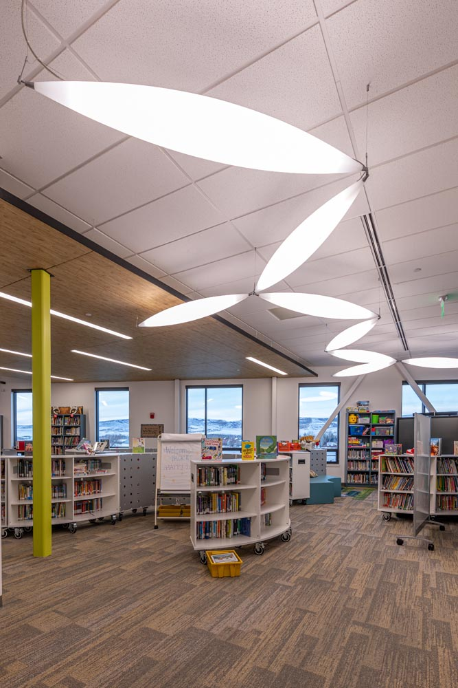 Library with leaf shape lighting hung from the ceiling.