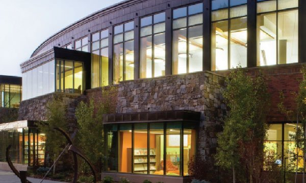 Library in Steamboat Springs with large windows lit up at night.