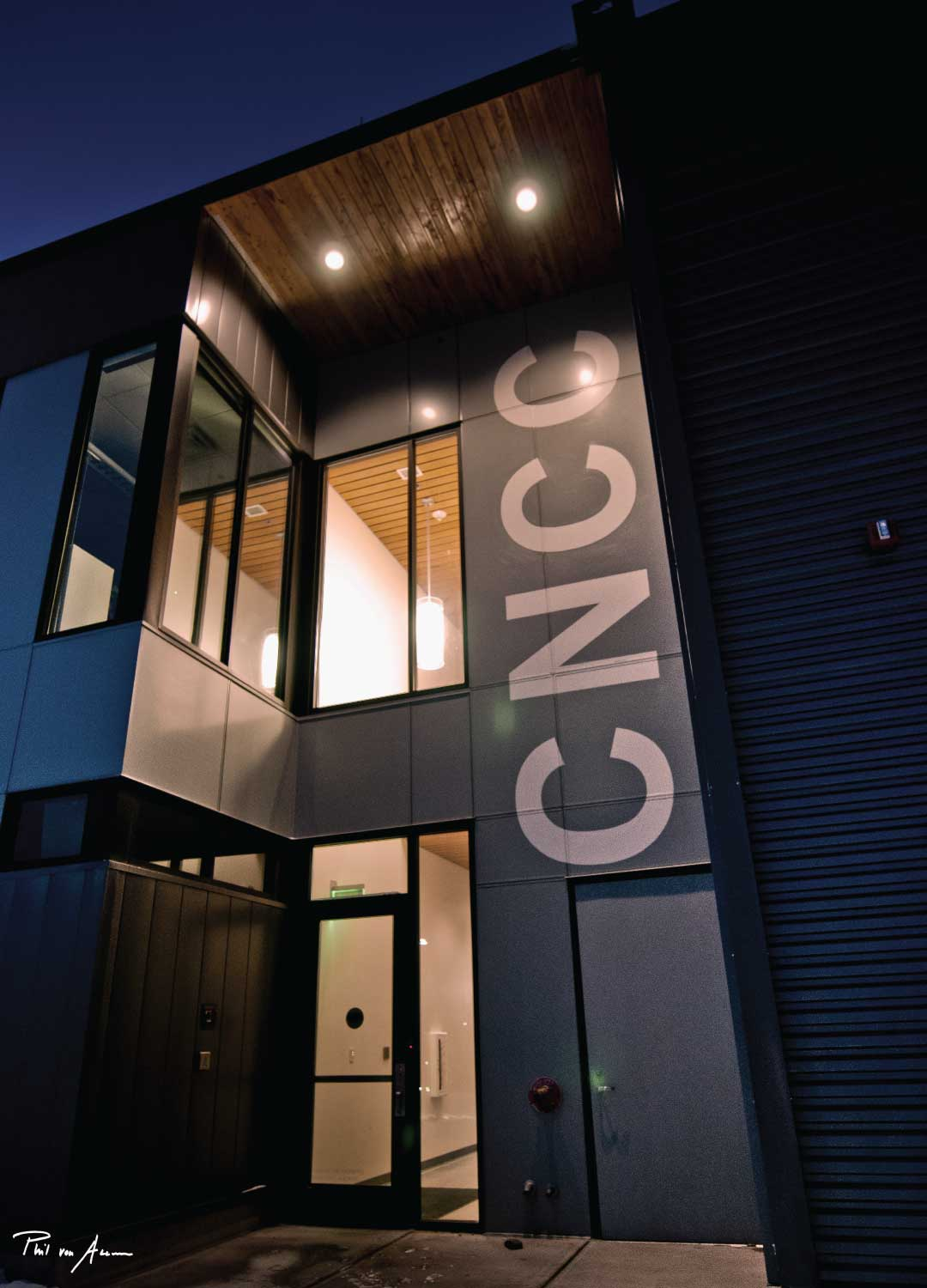 Entrance to CNCC building lit up at night.