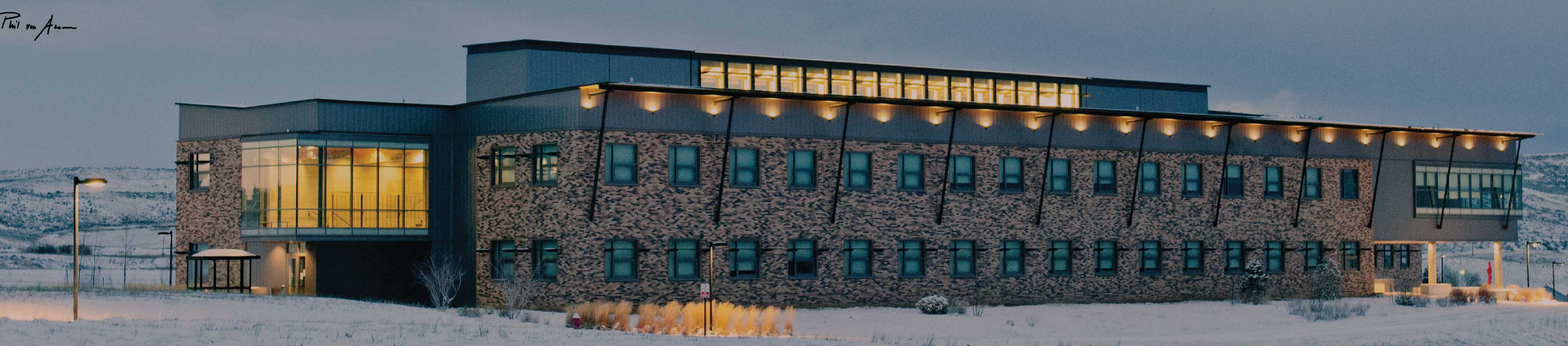 Exterior of the back CNCC building in the winter at night all lit up.