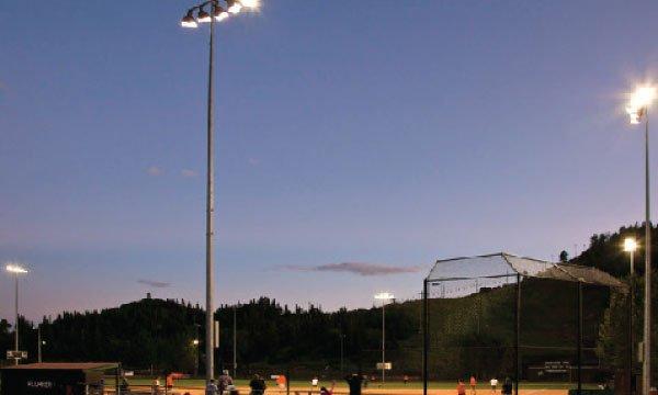 Large lighting post lighting up a baseball field at night.