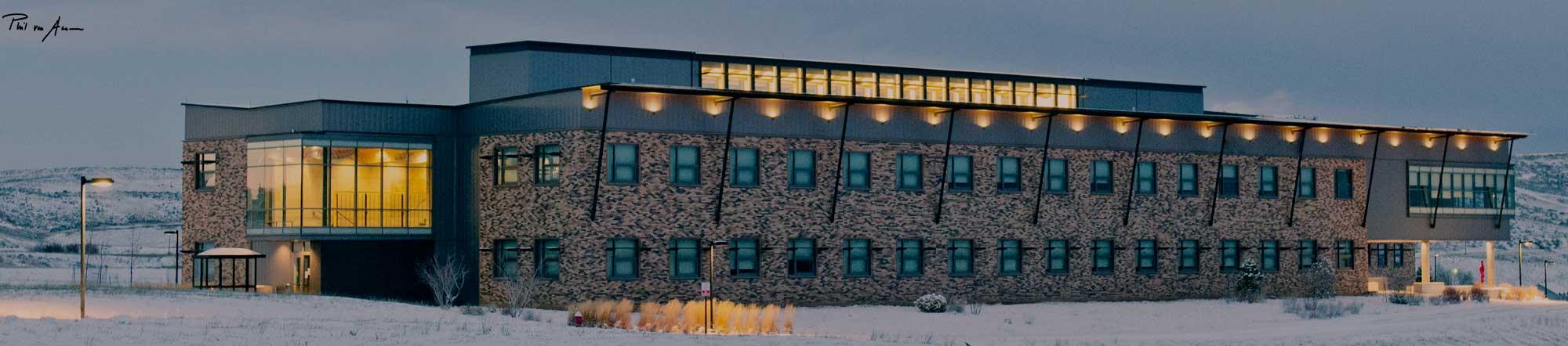 Large building at dusk lit up.