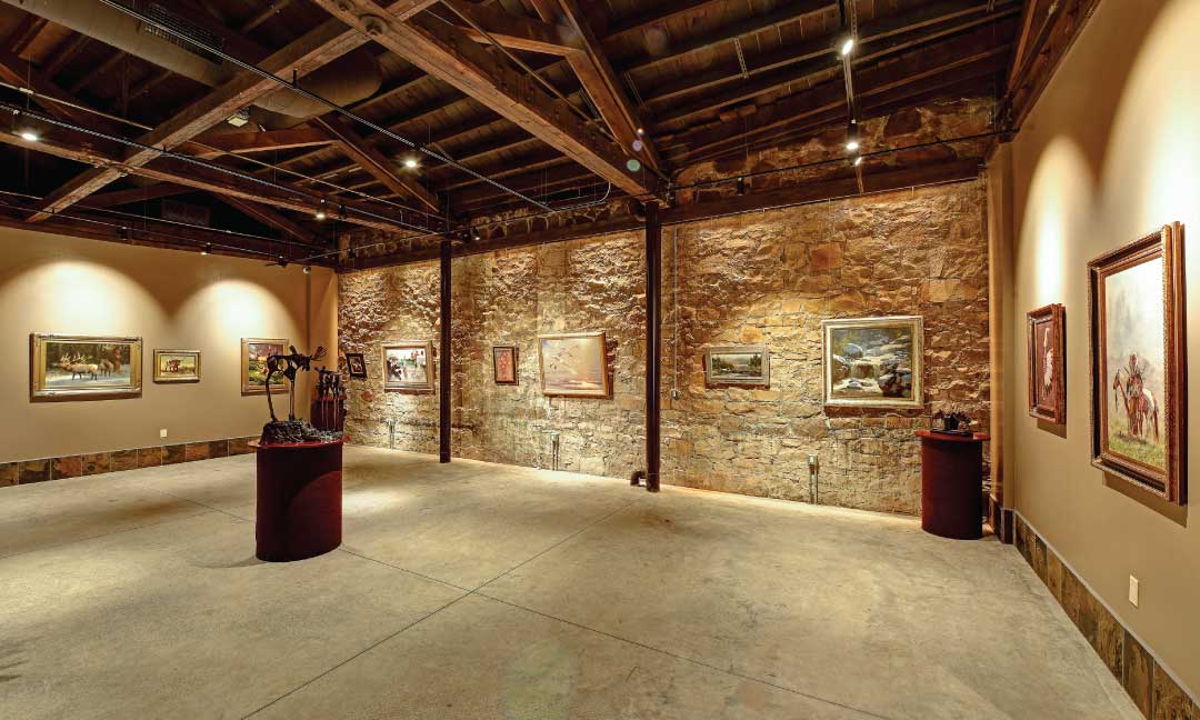 Gallery with lit up paintings and art on the walls.