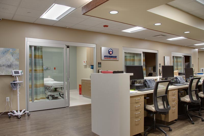Inside an ER showing the nursing station with a view to a room.
