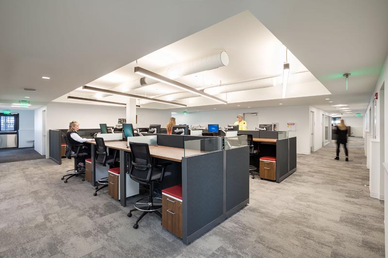 Open work space with desk and lighting set into ceiling.