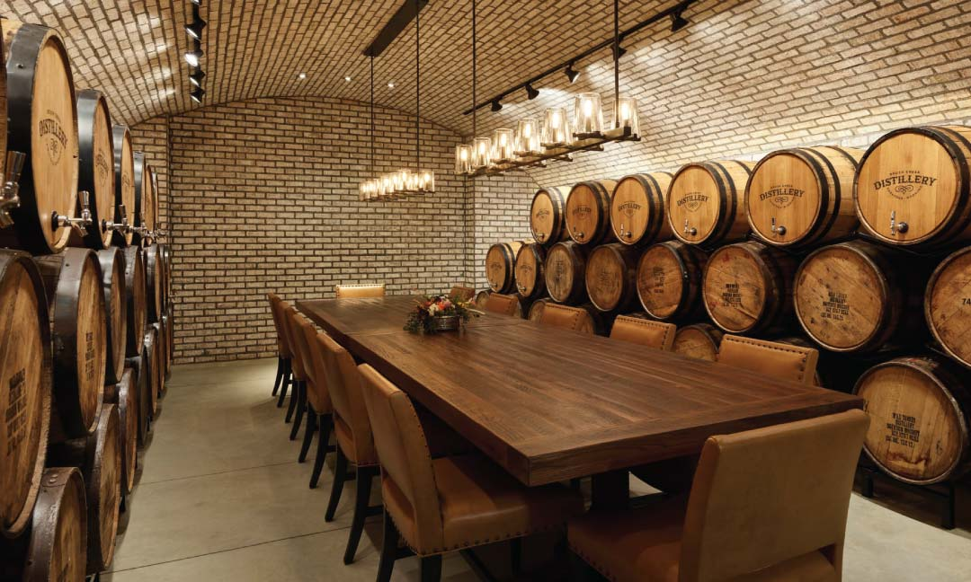 Inside a barrel room in a distillery with chandeliers over a dining table.