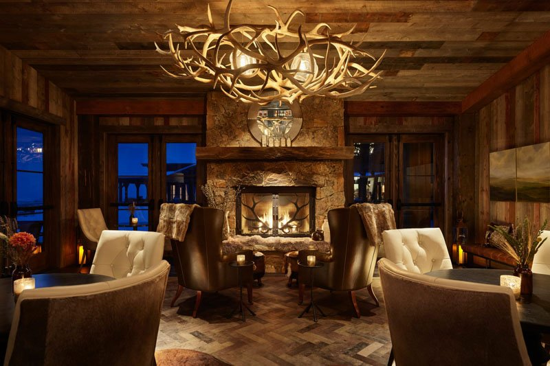 Fireplace mantle lit up and antler chandelier lighting up a sitting room.